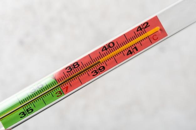 Primo piano medico del termometro a mercurio con una temperatura elevata di 38