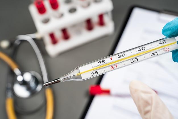 Termometro a mercurio medico con temperatura corporea elevata.