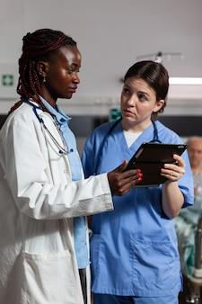 Infermiera medica che chiede consiglio al medico afroamericano