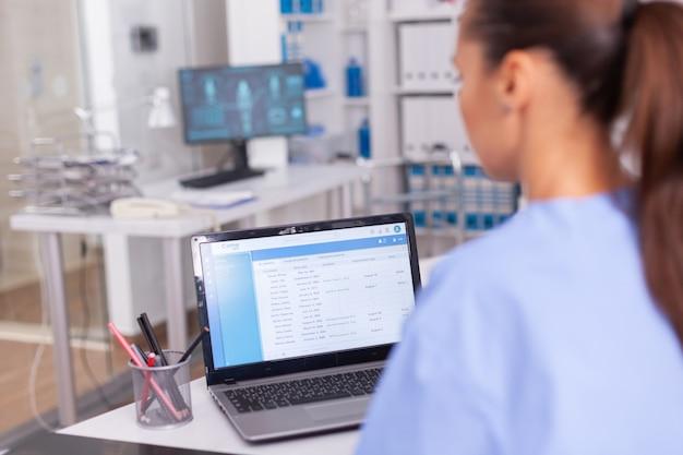 Infermiera medica che controlla la documentazione del paziente sul computer portatile nell'ufficio dell'ospedale. medico di assistenza sanitaria che utilizza computer in clinica moderna guardando monitor, medicina, professione, scrub.