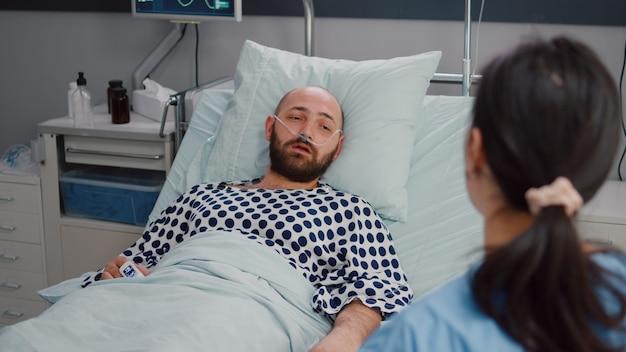 Infermiera medica che spiega i raggi x delle ossa all'uomo malato ricoverato durante il recupero della malattia