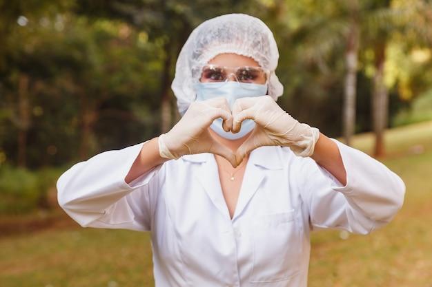 Infermiera medica che fa il cuore con la mano, indossando la mascherina chirurgica