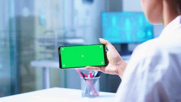 Infermiera medica che apre la porta di vetro dell'armadietto dell'ospedale e medico utilizzando smartphone con schermo verde. specialista sanitario in armadietto ospedaliero utilizzando smartphone con mockup.