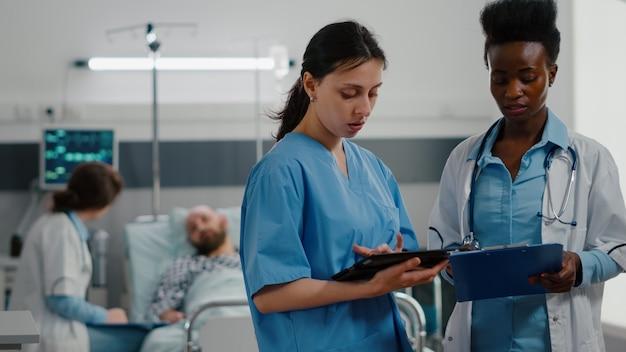 Infermiera medica che mostra competenza medica utilizzando computer tablet a specialista medico nero donna