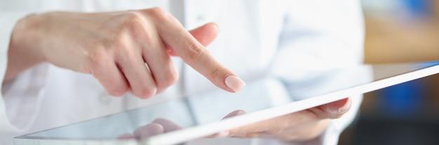 Il medico dell'ufficiale medico punta il dito sul tablet