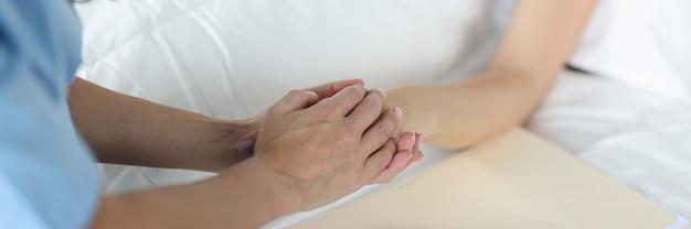 L'ufficiale medico tiene le cure mediche della mano dei pazienti e la cura del paziente nel concetto ospedaliero