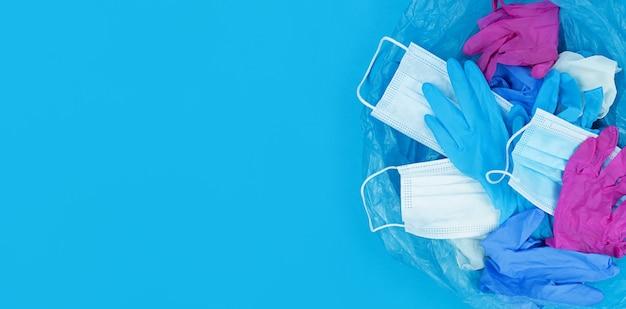 Rifiuti di coronavirus pandemia medica, maschere per il viso e guanti in lattice nel sacco della spazzatura su sfondo blu con spazio di copia.