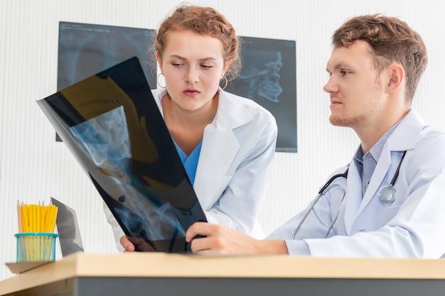 Raggi x e conversazione caucasici della tenuta dell'uomo dei professionisti medici sul paziente con la giovane donna di medico.