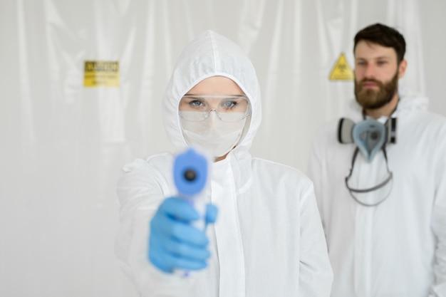 Professionisti medici in indumenti protettivi che misurano la febbre senza contatto presso il centro di test covid-19 durante l'epidemia di coronavirus.