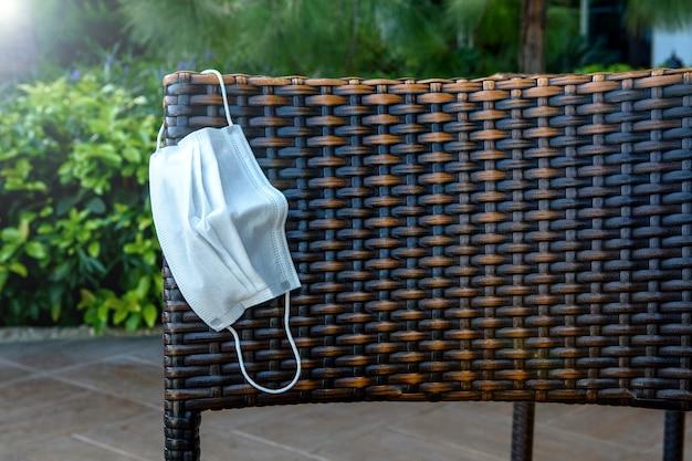 Maschera protettiva medica su una sedia in vimini in rattan in estate durante il coronavirus covid-19.