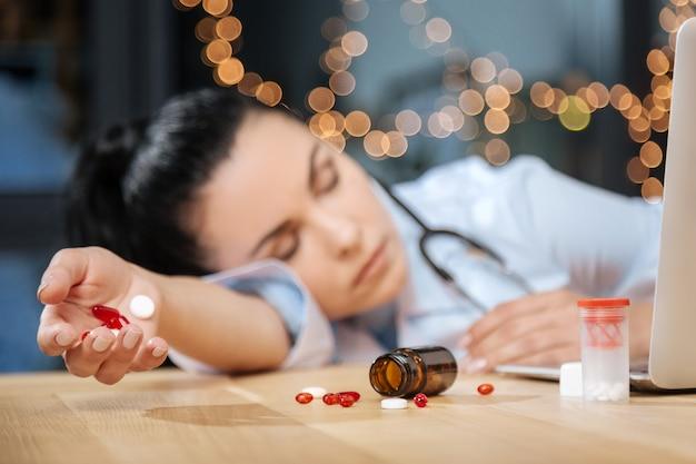 Ricerca medica. messa a fuoco selettiva di una bottiglia sdraiata sul tavolo e pillole sparse in giro con una bella scienziata stanca che dorme in background
