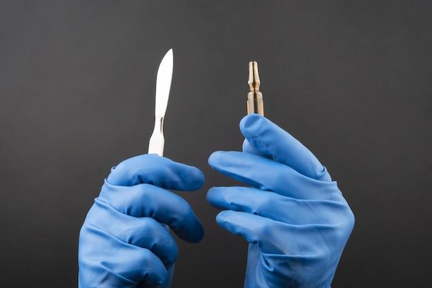 Bisturi medico e fiala per iniezione nelle mani che indossano guanti blu