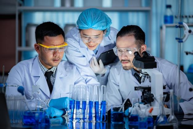 Ricerca tecnologica nel campo della scienza medica in laboratorio chimico, scienziato professionista che lavora per test di esperimenti nel lavoro di medicina sanitaria con attrezzature di vetro e liquido blu