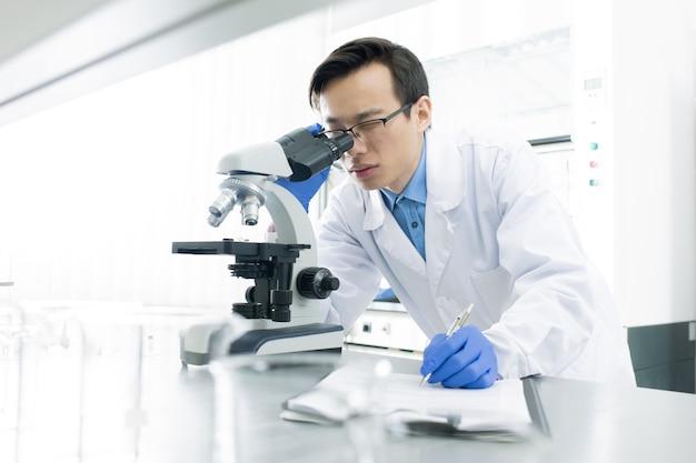 Scienziato medico utilizzando il microscopio
