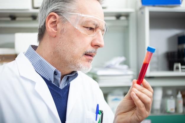Ricercatore medico sientista guardando una provetta di sangue, esame del sangue di coronavirus