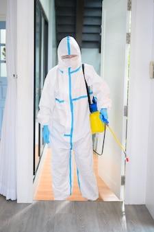 Uno staff medico in tuta dpi sta usando spray disinfettante in soggiorno, protezione covid-19, concetto di disinfezione.