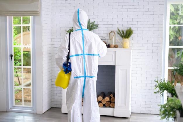 Uno staff medico in tuta dpi sta usando spray disinfettante in soggiorno, protezione covid-19