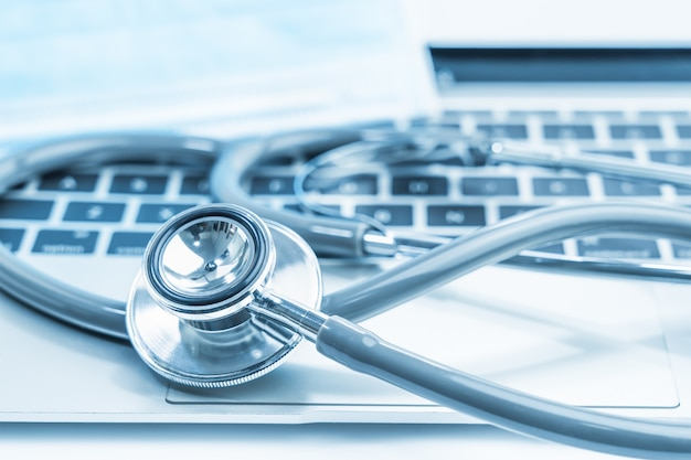 Stetoscopio medico per il controllo medico sul computer portatile con maschere facciali mediche come concetto medico