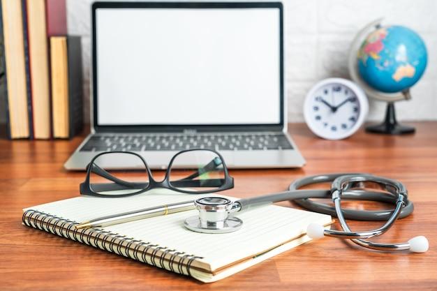 Stetoscopio medico per controllo medico con computer portatile sul blocco note medico come concetto medico