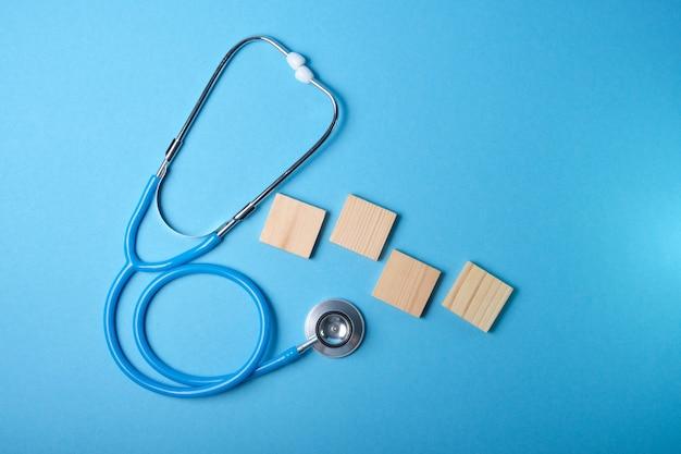 Stetoscopio medico e quattro quadrati di legno su una superficie blu