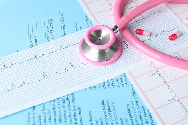 Stetoscopio medico, pillole e cardiogramma sul tavolo. concetto di cardiologia
