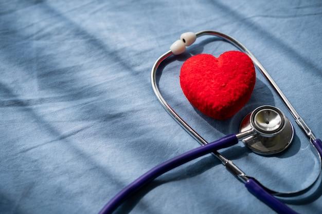 Stetoscopio medico e cuore rosso sul letto del paziente. assistenza sanitaria di concetto.