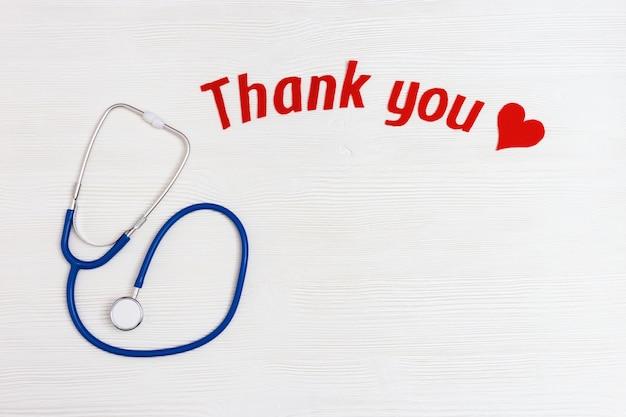 Stetoscopio medico, cuore rosso e testo di ringraziamento