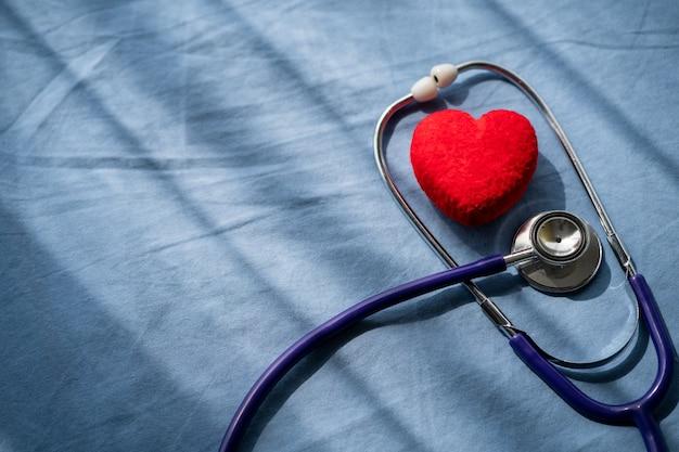 Stetoscopio medico e cuore rosso con cardiogramma. assistenza sanitaria di concetto.