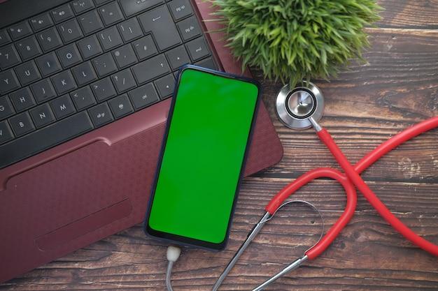 Stetoscopio medico e smart phone su laptop su tavola di legno