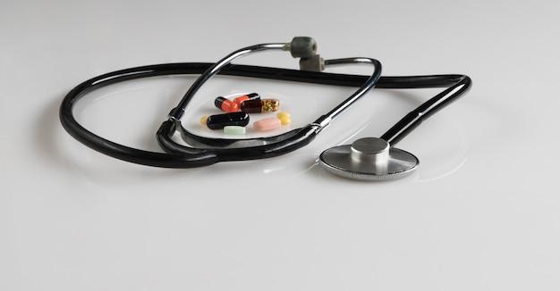 Stetoscopio medico con pillole su sfondo bianco, isolato