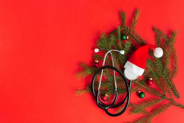 Stetoscopio medico con cappello di babbo natale e albero di natale su sfondo rosso