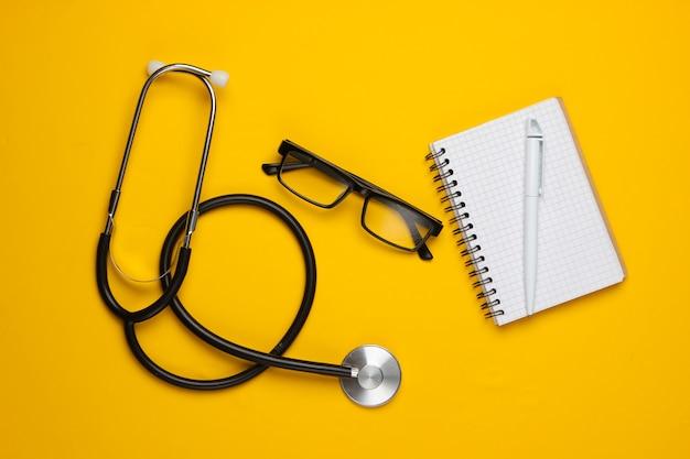 Natura morta medica su un giallo. stetoscopio, occhiali, blocco note.