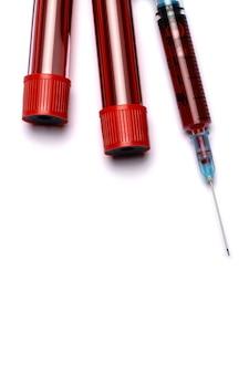 Siringa medica e provetta di plastica isolata su bianco
