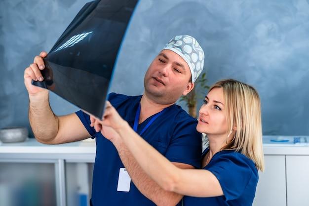 Equipe medica che discute la diagnosi dell'immagine a raggi x in ufficio. medici uomo e donna.