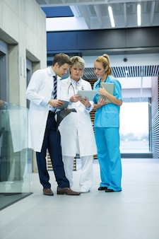 Equipe medica discutendo su tavoletta digitale in corridoio