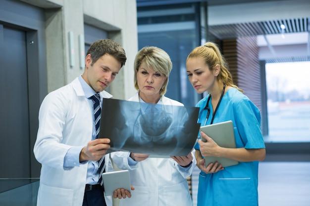 Squadra medica che esamina il rapporto dei raggi x nel corridoio