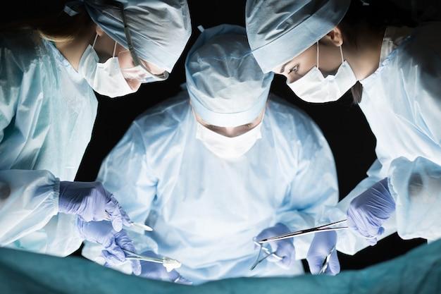 Equipe medica durante l'operazione. gruppo di chirurgo al lavoro in sala operatoria