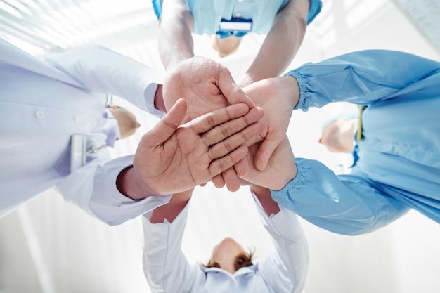 Equipe medica che impila le mani