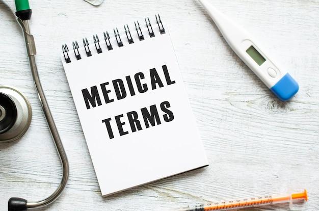 Termini medici è scritto in un taccuino su un tavolo di legno chiaro accanto a uno stetoscopio. concetto medico