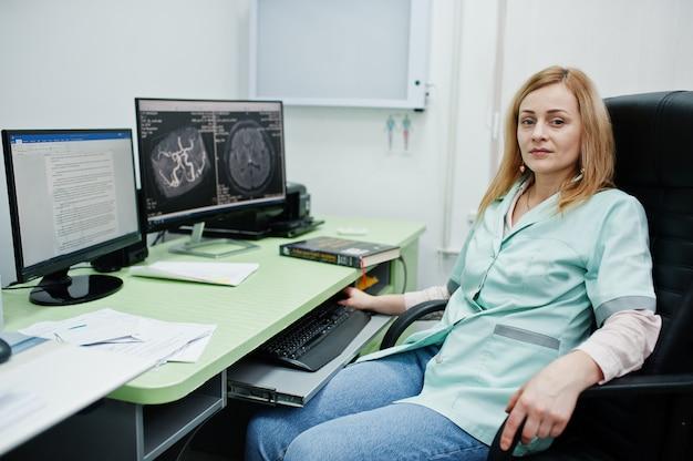 Tema medico. dottore nell'ufficio di risonanza magnetica presso il centro diagnostico in ospedale, seduto vicino ai monitor del computer.