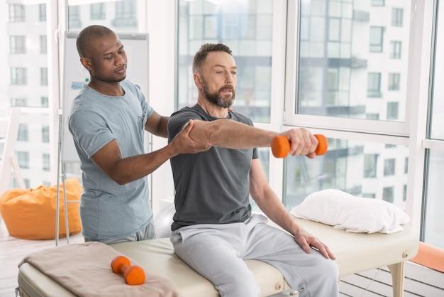 Terapista medico. piacevole simpatico dottore in piedi dietro il suo paziente mentre lo aiuta ad alzare una mano con un manubrio
