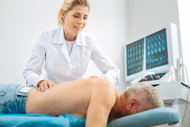 Terapia medica. medico femminile felice professionista che sorride e che fa un massaggio mentre lavorava con il suo paziente