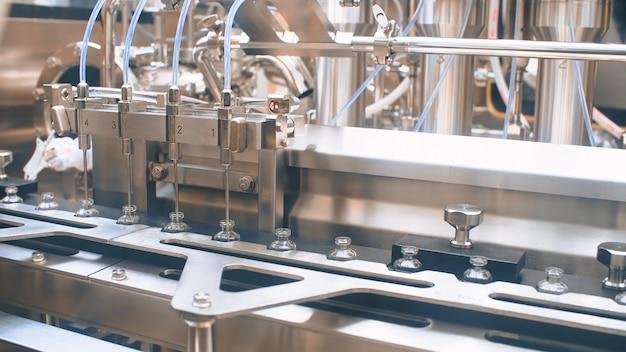 Fiale mediche su una linea di produzione automatica per il riempimento di vaccini e iniezioni. coronavirus