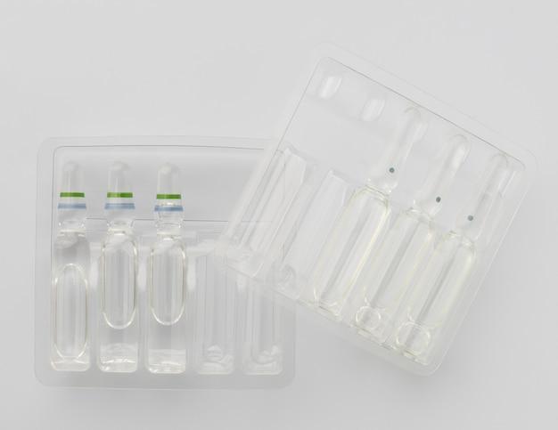 Fiale mediche con liquido per iniezione in contenitori di plastica su sfondo bianco