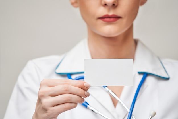 Medico o infermiere dell'operaio medico che mostra biglietto da visita in bianco