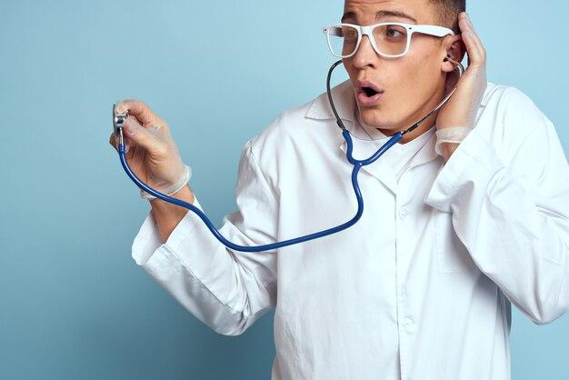 Il lavoratore medico in vestaglia e occhiali tiene uno stetoscopio