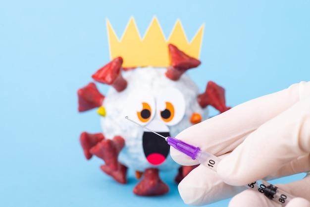 Lavoratore medico tenendo una siringa con vaccino contro il virus covid-19. modello di coronavirus dei cartoni animati spaventato e scioccato sullo sfondo