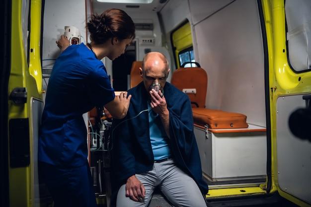 Operaio medico che fornisce assistenza psicologica a un uomo salvato dall'incendio