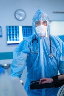 Operatore medico che indossa dpi in unità operativa. lotta alla diffusione del coronavirus. maschera, occhiali protettivi e tuta protettiva.