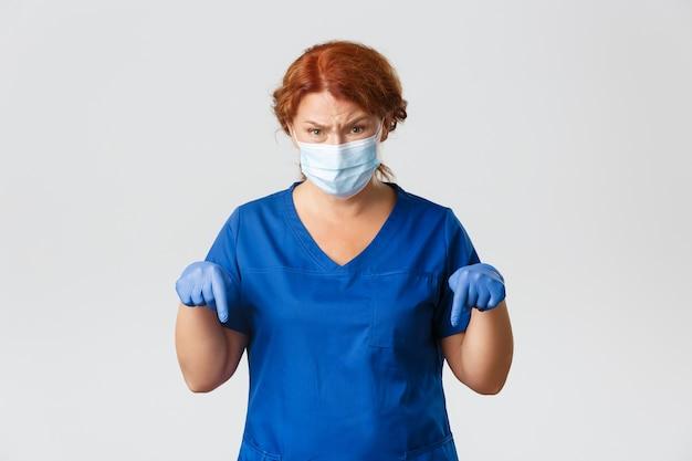 Operatori sanitari, pandemia covid-19, concetto di coronavirus. dottoressa frustrata e distrutta, infermiera in maschera e guanti rivolti verso il basso verso qualcosa di disgustoso, sfondo grigio.
